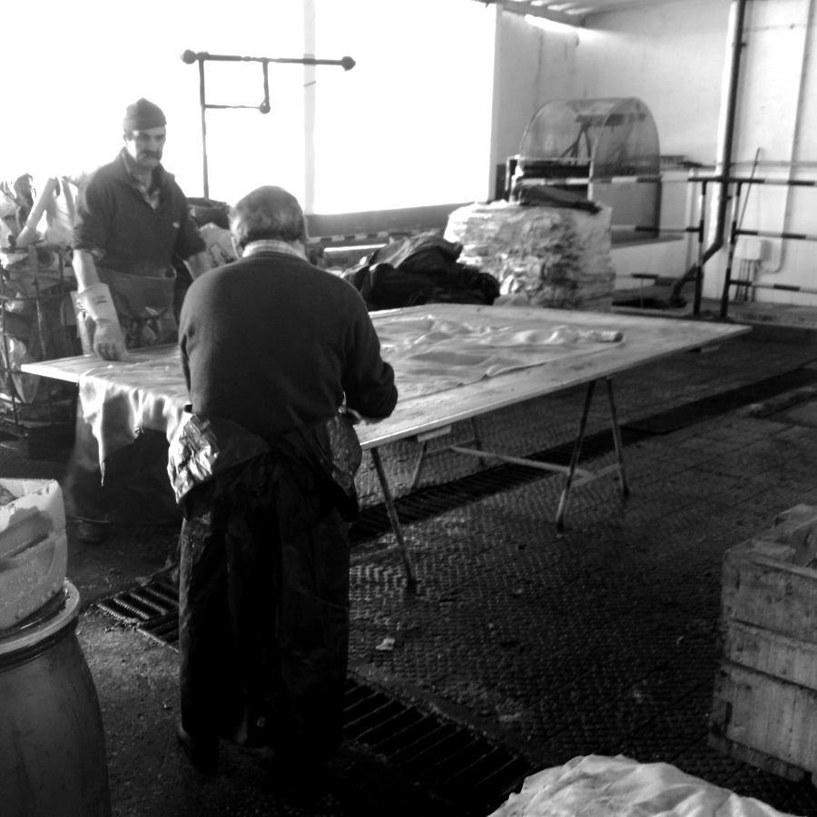 Men cutting raw leather material.